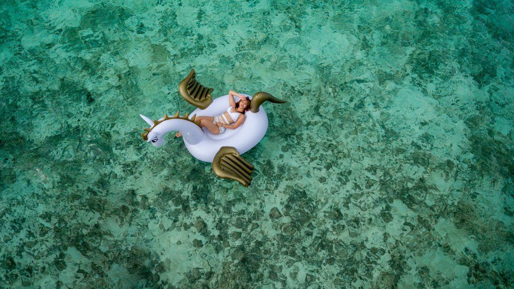 Femme sur une bouée licorne au milieu de la mer